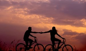 Couples Counseling Brentwood & Nashville, TN - couple holding hands bike riding at sun set.