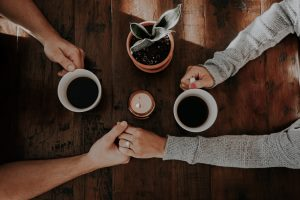 Brentwood couples counseling - Couple holding hands over coffee