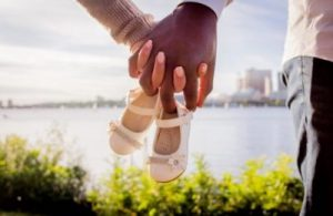 marriage counseling brentwood - couple holding hands and baby shoes